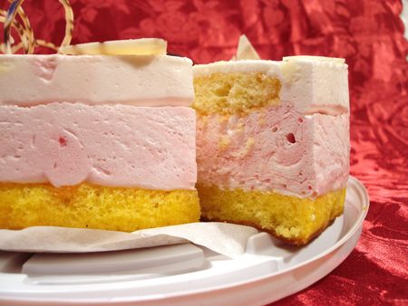 white and pink cake over red background