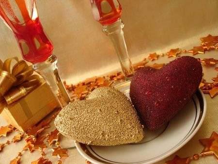golden and red hearts, gift box and glasses on celebratory table photo