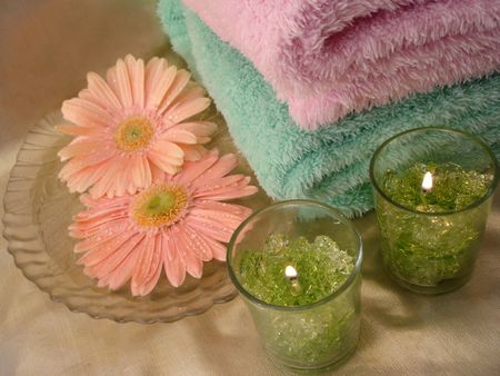 Spa essentials (green candles and towels with flowers) photo