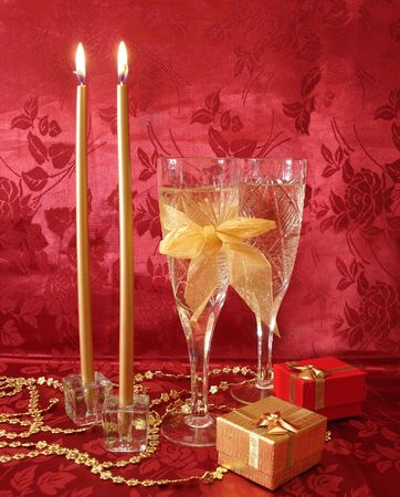 Two wine glasses with champagne, gifts and golden candles on red background