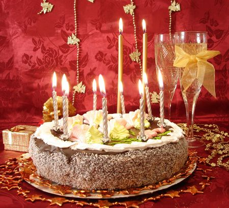 celebratory table (cake and candles, two glasses with champagne, gift boxes) on red Stock Photo - 763809