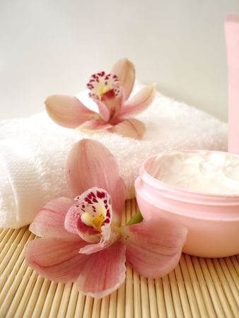 container of cosmetic moisturizing cream with pink orchids and towel photo