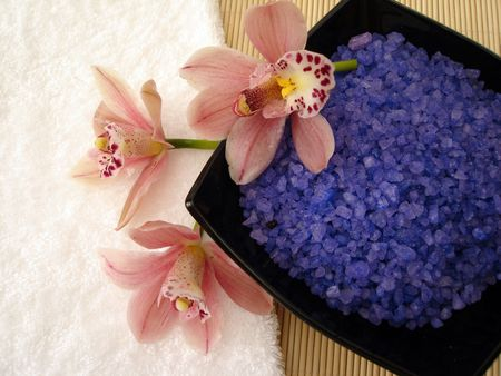 Spa essentials (violet salt, white towel and pink orchids) photo