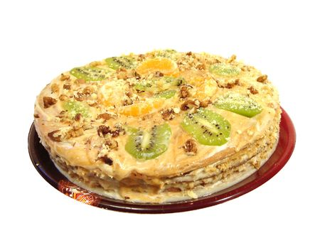 cake with kiwi, nuts and tangerine on plate over white background photo