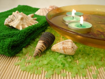 green towel, shells, candles in plate with water and salt on a straw mat  photo