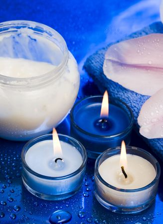 spa essentials, cream, candles with flower on blue background  Stock Photo - 2962450