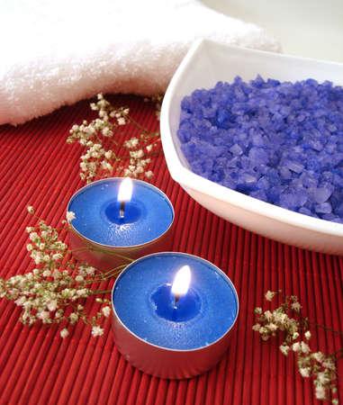 Spa essentials (blue salt, towels, candle and flower)