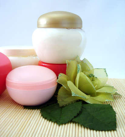 moisten: containers of cosmetic moisturizing cream with green flower