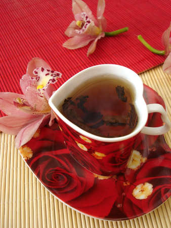 red cup of tea in the form of heart with pink orchids over straw matt
