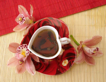 matt: red cup of tea in the form of heart with pink orchids over straw matt   Stock Photo