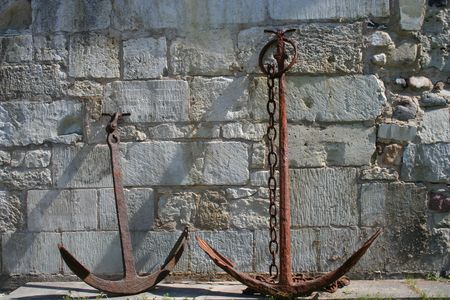 Two old anchors against a stone wall