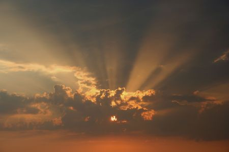 Solar rays through clouds at sunset