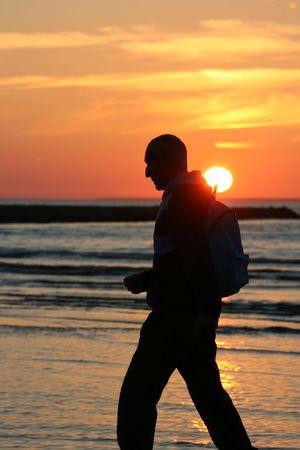 Old man walking at sunset