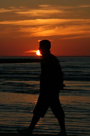 Young man walking at sunset
