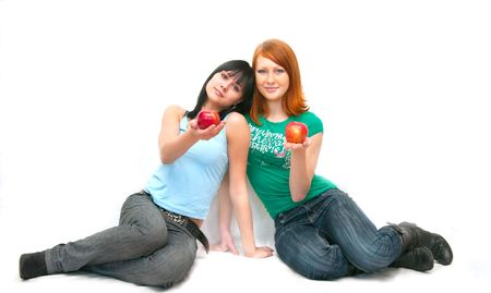 The image of two girls stretching apples photo