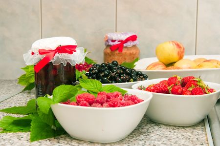 The image of jars with jam and fresh berries on a wooden table photo