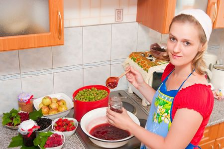 The image of the woman preparing jam from berries on kitchen photo