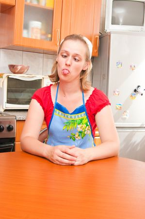 messy kitchen: The tired housewife puts out the tongue