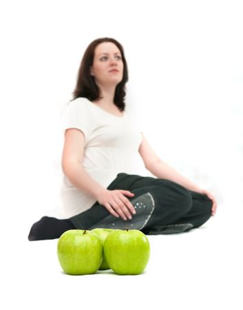 The image of green apples against the pregnant woman. Focus on apples photo