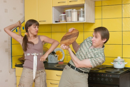 dominating: The image of the woman beating the man on kitchen