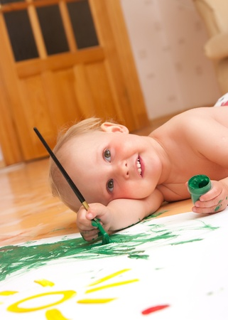The little girl draws lying on a floor photo