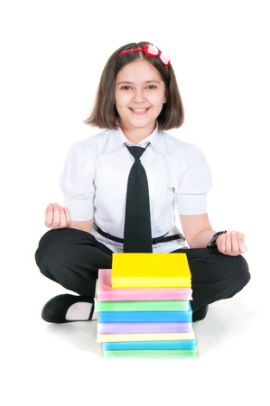 meditates: The schoolgirl meditates before textbooks