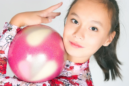 caved: Beautiful Asian girl gymnast with a ball on white background