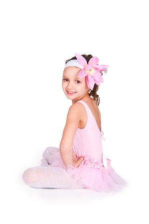 Full-length portrait of a little girls practicing her ballet kicks on a white background photo