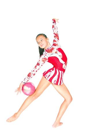 Gimnasta hermosa niña de Asia con una pelota en el fondo blanco