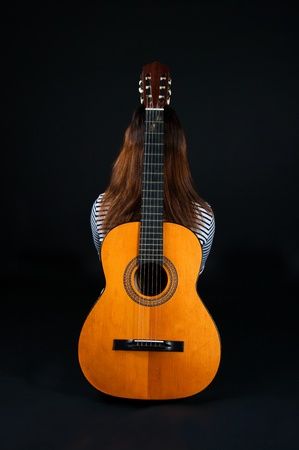 leaned: The image of the girl with a guitar on a black background Stock Photo