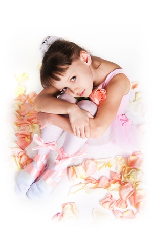 The small tired ballerina sits on a floor in rose-petals photo