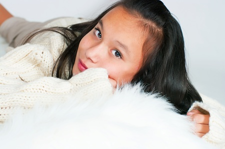 lie forward: The beautiful Asian girl in a knitted sweater