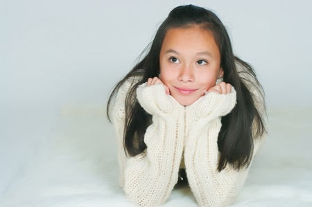 laying forward: The beautiful Asian girl in a knitted sweater