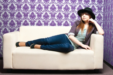 The fashionable girl on a light sofa photo