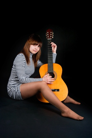 The image of the girl with a guitar on a black background photo
