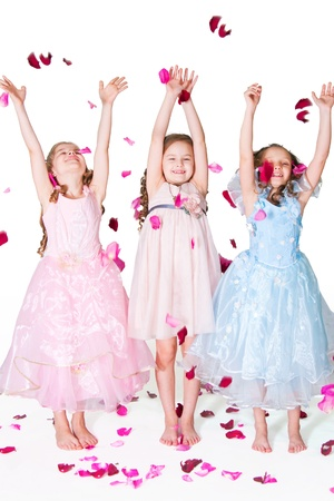 Three elegant girls on with rose-petals on a white background photo