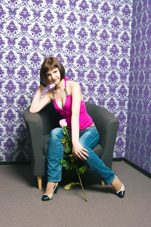 The fashionable girl on a brown chair Stock Photo - 13557149