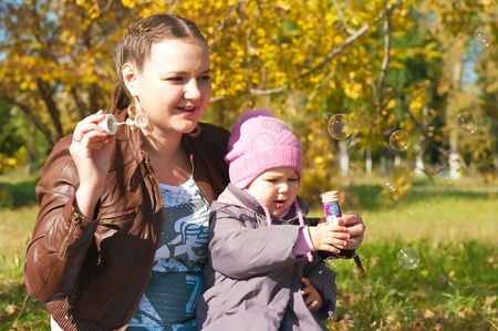 The young woman with the daughter on walk in park photo