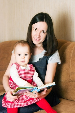 Mother reading to young daughter photo