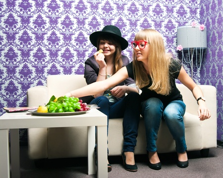Two girlfriends sat down on a sofa photo