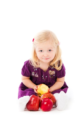 Little girl wiht apple on white background photo
