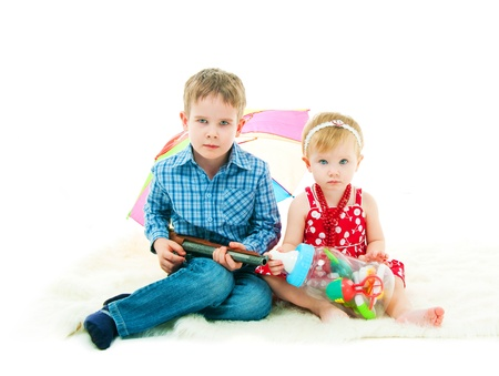 The brother and the sister with toys sit on a floor photo