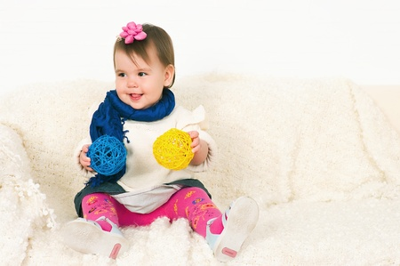 12 18 months: The image of the little girl sitting on a sofa Stock Photo