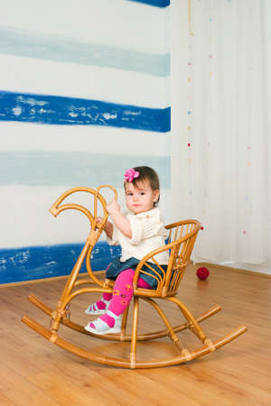 The image of the little girl on a horse rocking chair photo