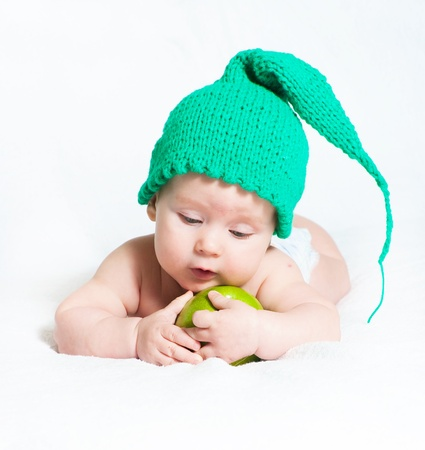 The kid in a green cap with apple photo
