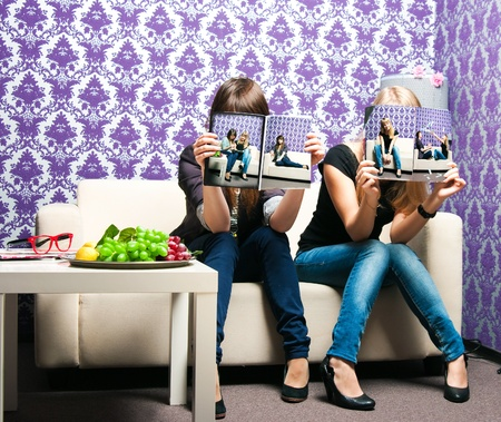 Two girlfriends on a sofa read the magazine photo