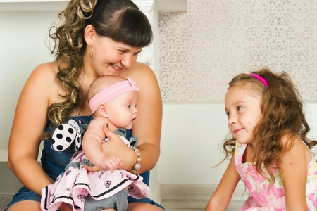2 5 months: mother cheerfully spends time with daughters Stock Photo