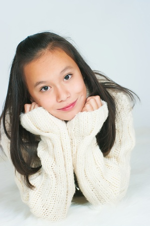 lies forward: The beautiful Asian girl in a knitted sweater