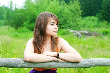 Beautiful woman smiling leaning against a wooden fence Stock Photo - 17755769