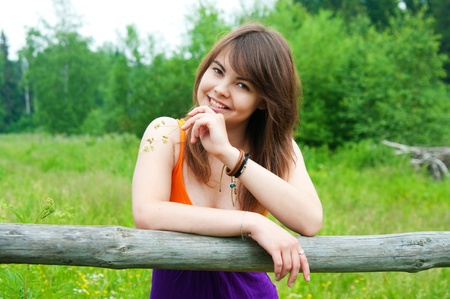 Beautiful woman smiling leaning against a wooden fence Stock Photo - 17755767